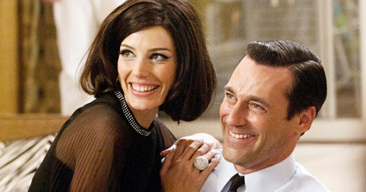 Don and Megan Draper getting cozy on a couch in a scene from Mad Men