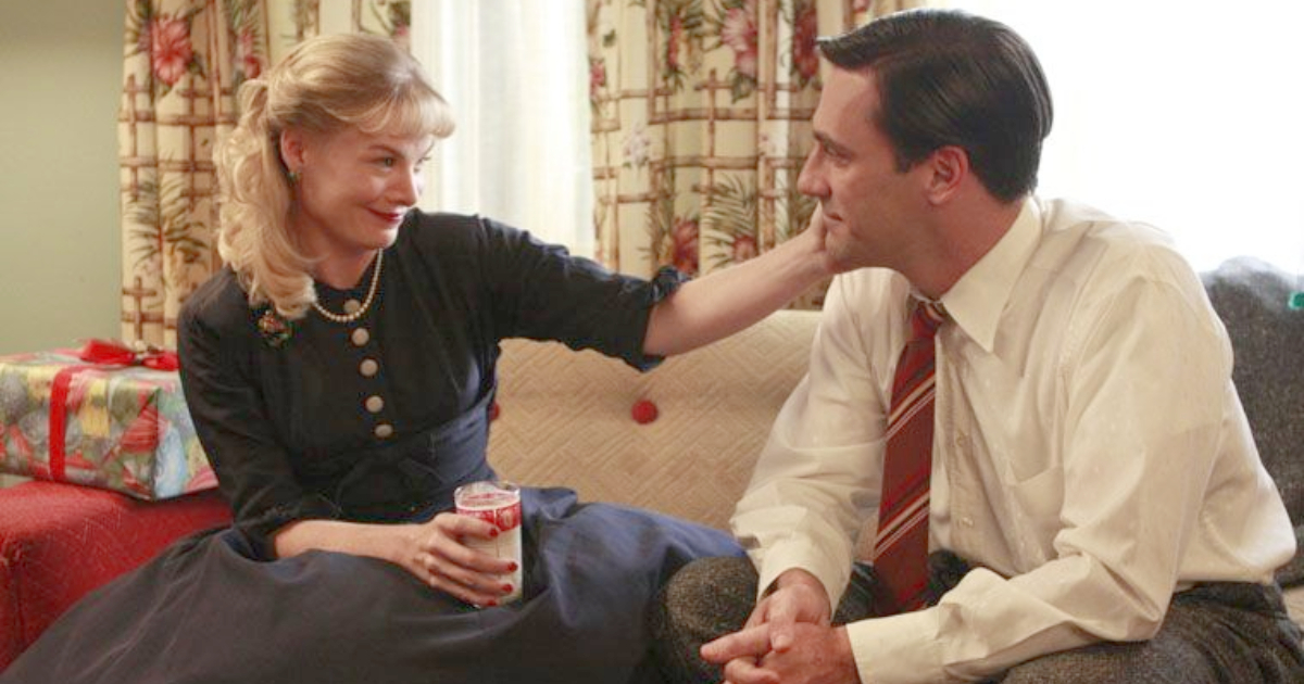 Anna and Don Draper sitting on the couch together drinking milk in a scene from Mad Men