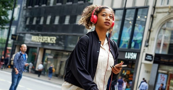 Romance Podcasts, photo of a black woman with her hair pulled back walking down the street and listening to a podcast on her phone, books