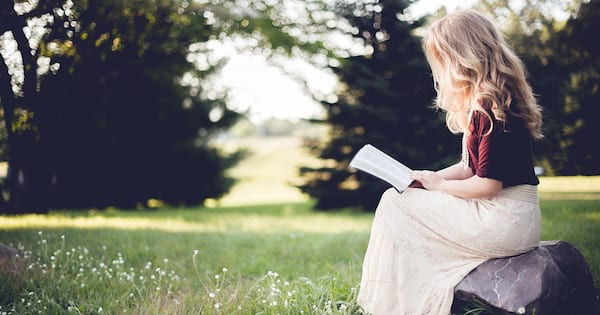 Romance Tropes, image of a blonde white woman in profile reading a book, books