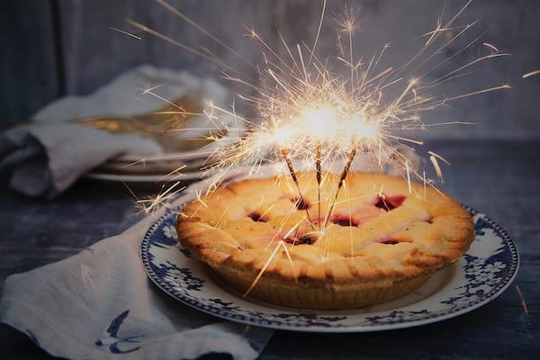 a cherry pie on a blue and white porcelain plate with three lit sparkler candles