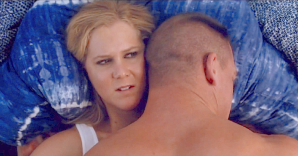 Amy Schumer in bed with John Cena in a scene from Trainwreck