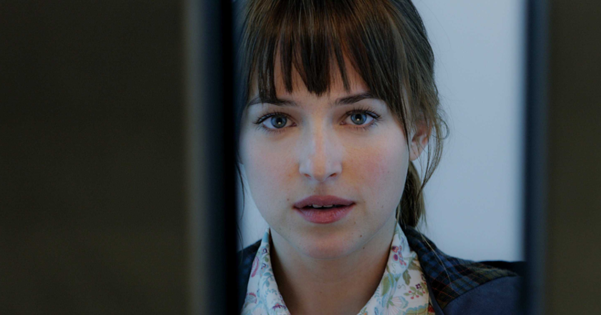 Ana peering into a window in a scene from Fifty Shades of Grey
