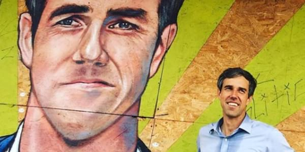 a picture of presidential candidate Beto O'Rourke standing next to a painted mural of his face