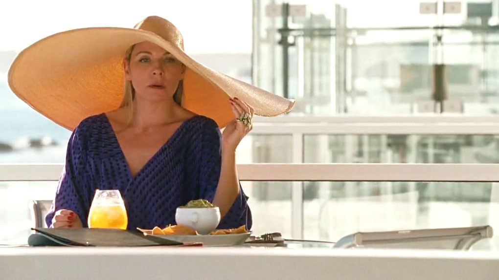 Samantha eating chips and guac on her balcony in a scene from Sex and the City