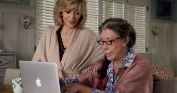 Frankie typing on her laptop while Grace watches over her shoulder in a scene from Grace and Frankie