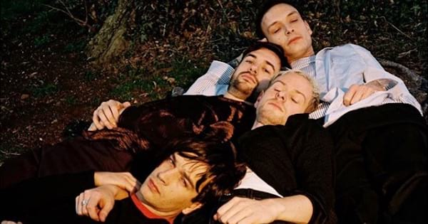 the 1975 band laying in grass