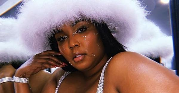 lizzo posing with white fur hat