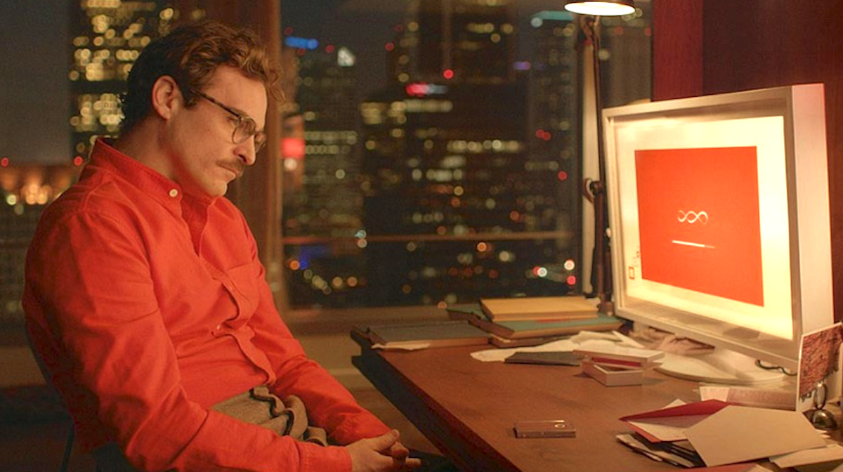 Joaquin Phoenix sitting at a desk in a red shirt looking at a computer screen in a scene from the movie 'Her'