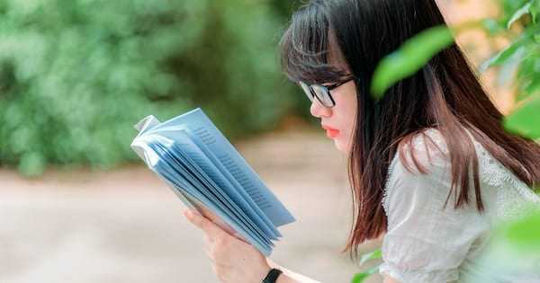 Romance and Sex Positivity, profile of an Asian woman wearing orange lipstick reading a book, books