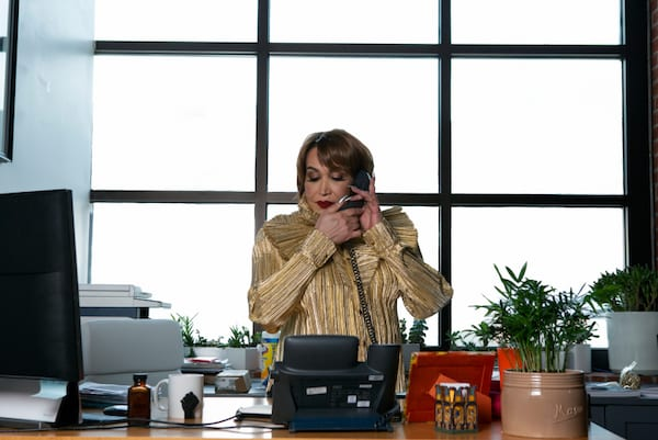 A transfeminine executive using the phone in her office