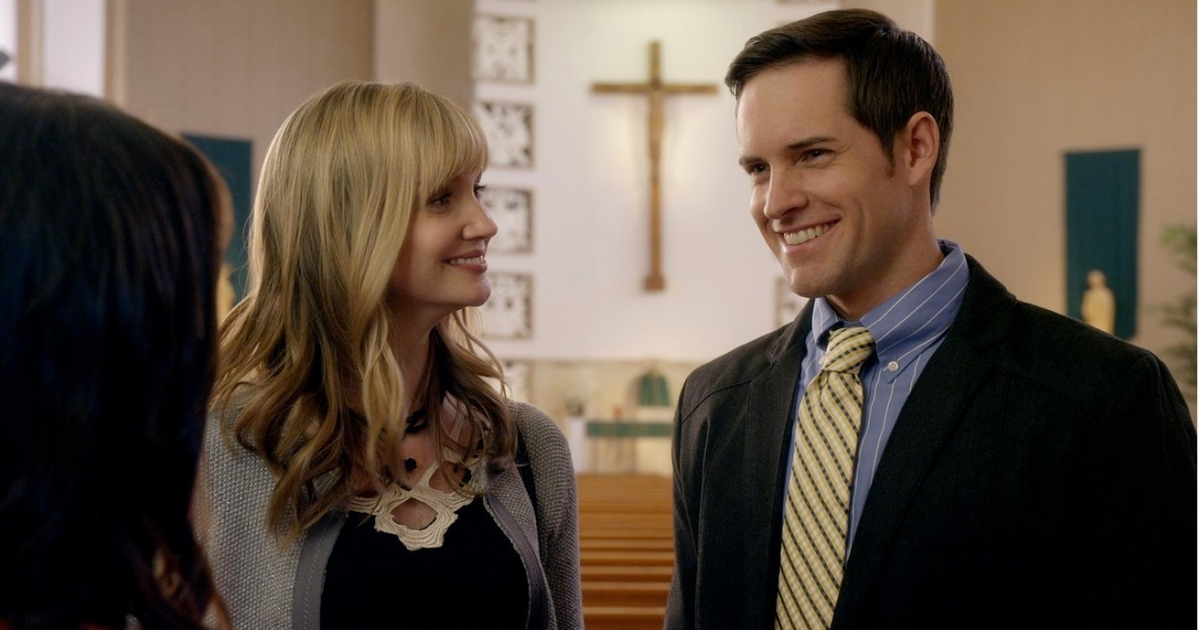 Two people chatting in church with a cross behind them