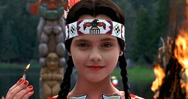 Wednesday Addams dressed up as Pocahontas with a lit match in her hand