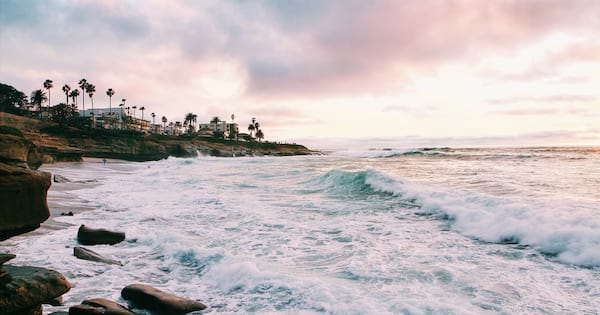 Inspirational Poetry Quotes, image of the ocean tide hitting the rocky shore with houses visible in the background, books