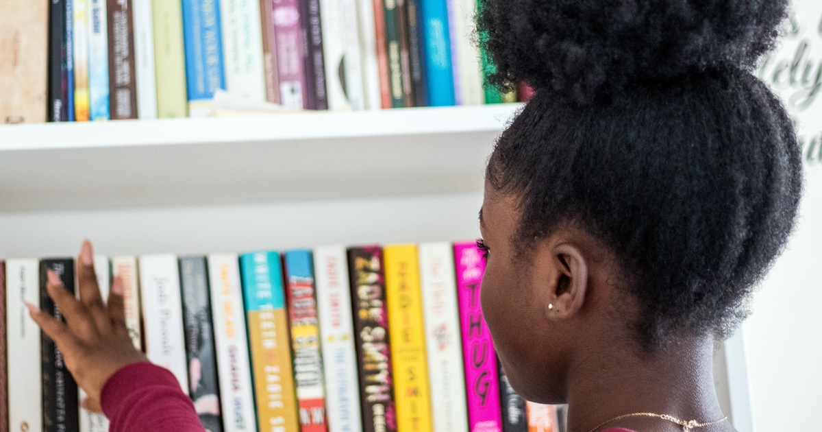Bookstore Romance Day, a black woman looking at books on a shelf, books