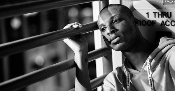 Poems About Depression, black and white photo of a black man leaning against bars and looking sorrowful, books