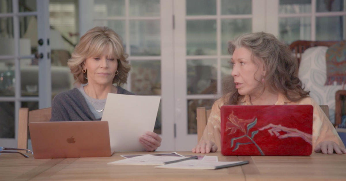 Grace and Frankie filling out papers while sitting in front of laptops