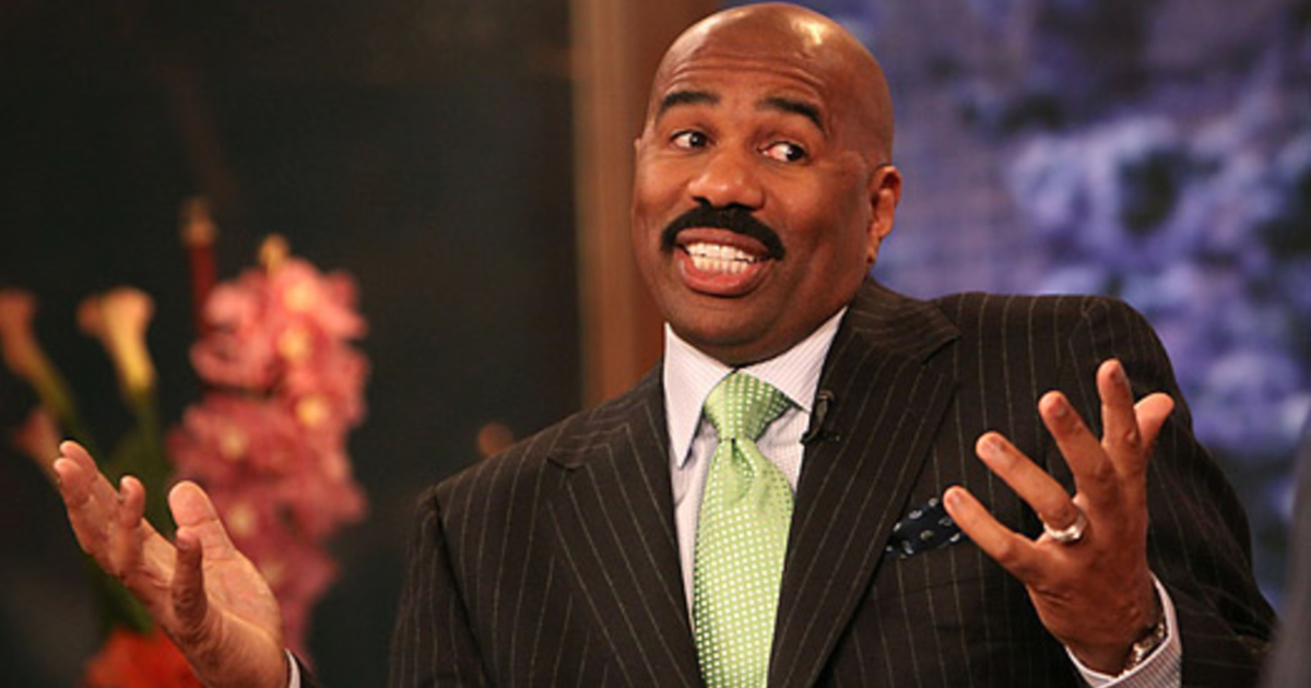 Steve Harvey sitting down and shrugging his shoulders