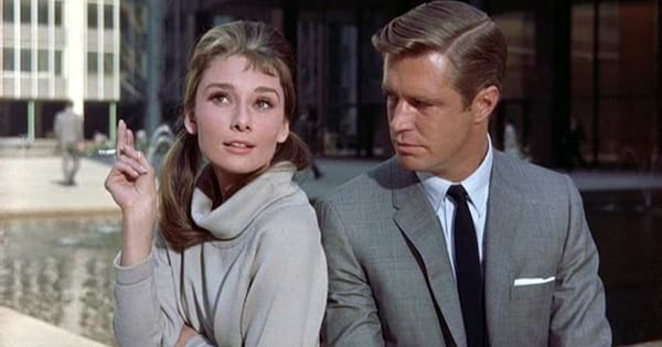 Audrey Hepburn smoking a cigarette next to George Peppard in 'Breakfast at Tiffany's'