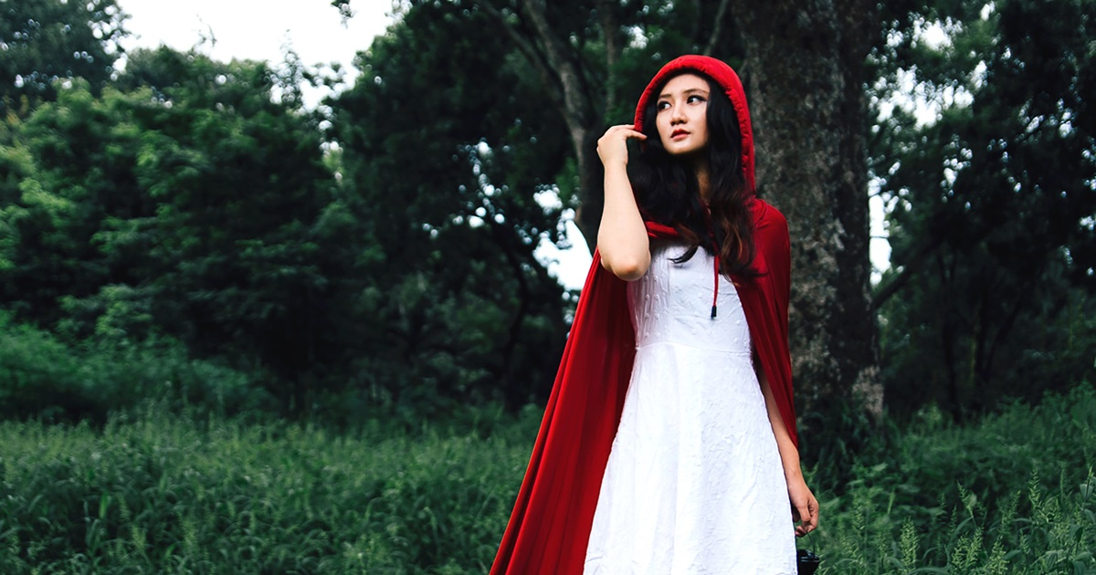 Romantic Retellings, photograph of an Asian woman dressed as Little Red Riding Hood, books