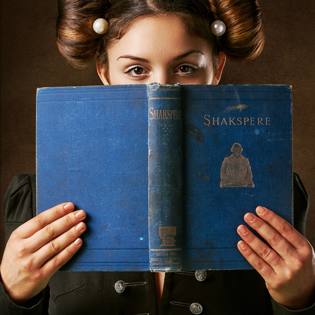 Shakespeare Quotes About Friendship, image of a woman with her hair in two buns holds a blue Shakespeare book in front of her face, books