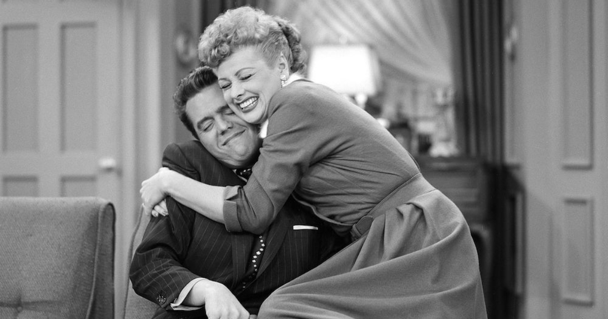 Lucille Ball hugging Ricky Ricardo while he's sitting on the couch in a scene from I Love Lucy