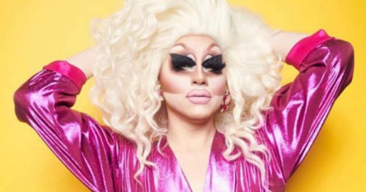 Drag queen Trixie Mattel wearing all pink and posing in front of a solid yellow backdrop