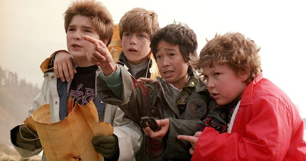 Mikey, Chunk, mouth, and Data holding a map and pointing at an abandoned restaurant in 'The Goonies'
