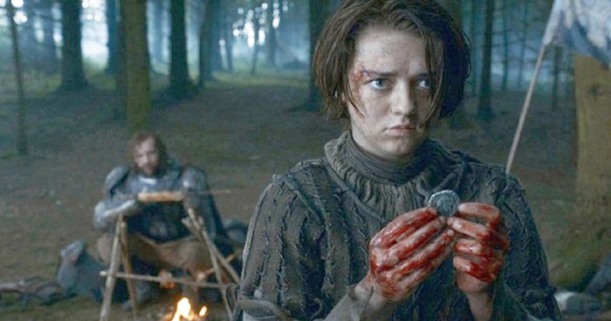Arya Stark holding a coin with her blood-soaked hands in an episode of Game of Thrones