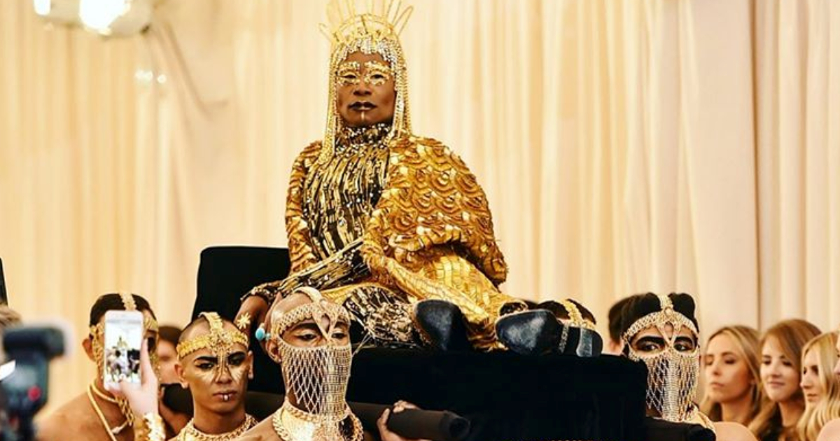 Billy Porter dressed as an Egyptian pharaoh being carried in on a bed by a harem of men at the 2019 Met Gala