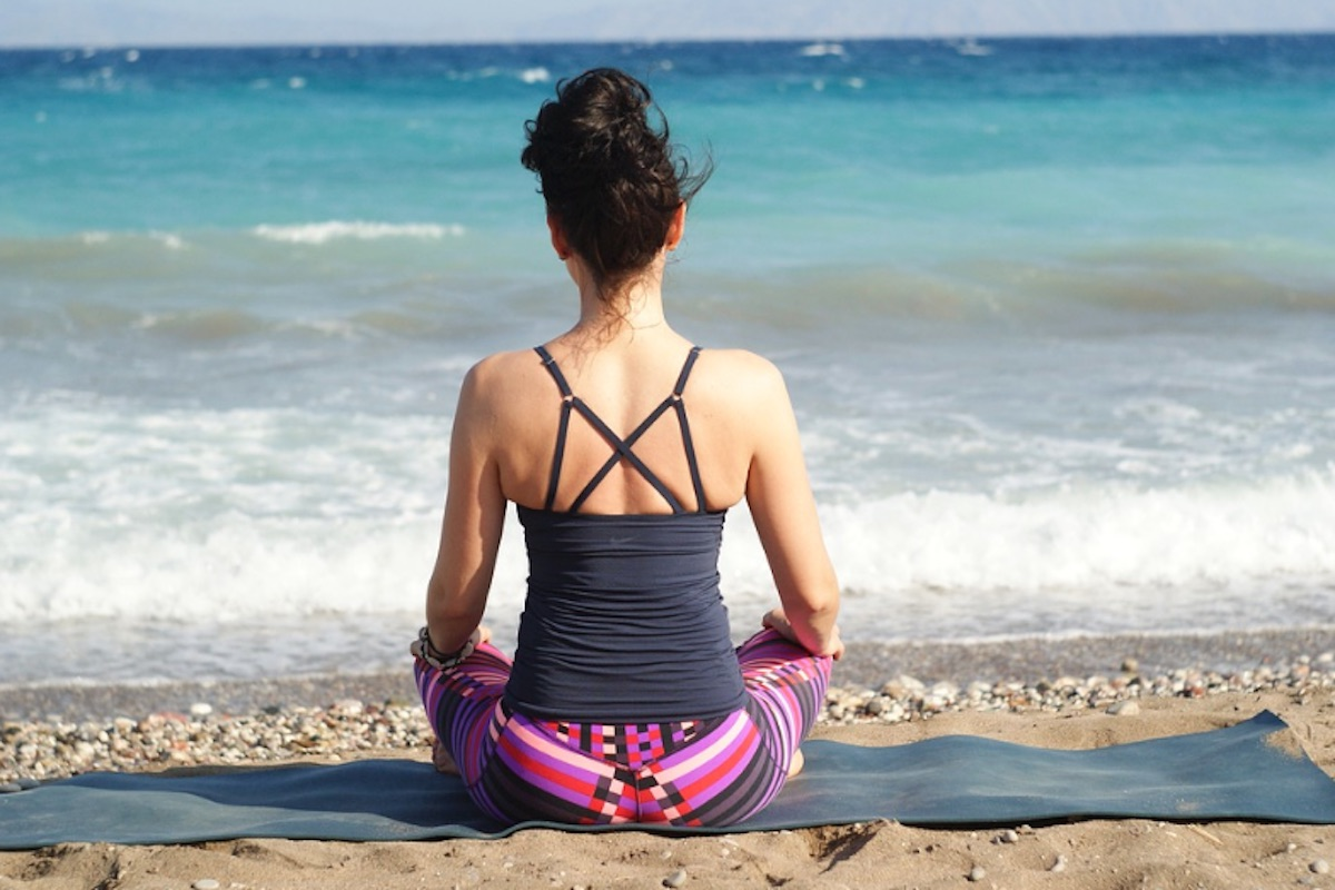 woman sitting practicing yoga on the beach quotes