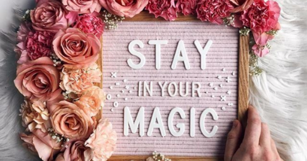 Pink felt letter board with the saying \Stay in your magic\ written on it and adorned with pink-toned flowers
