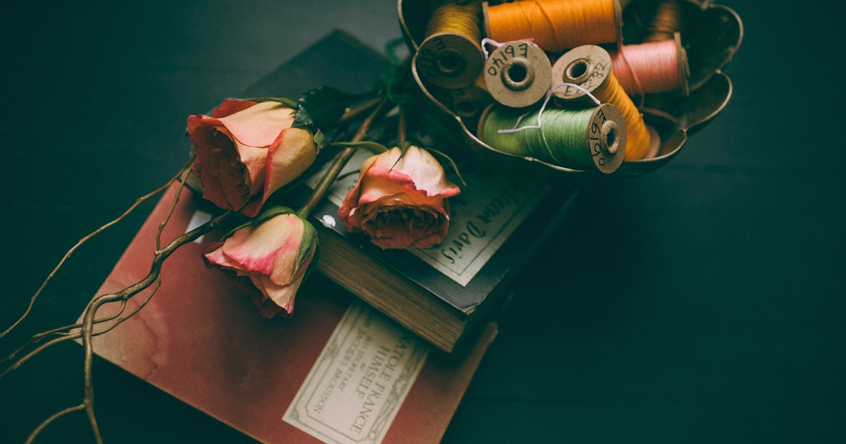 Find the title of romance novel, image of books with roses and spools of thread, books