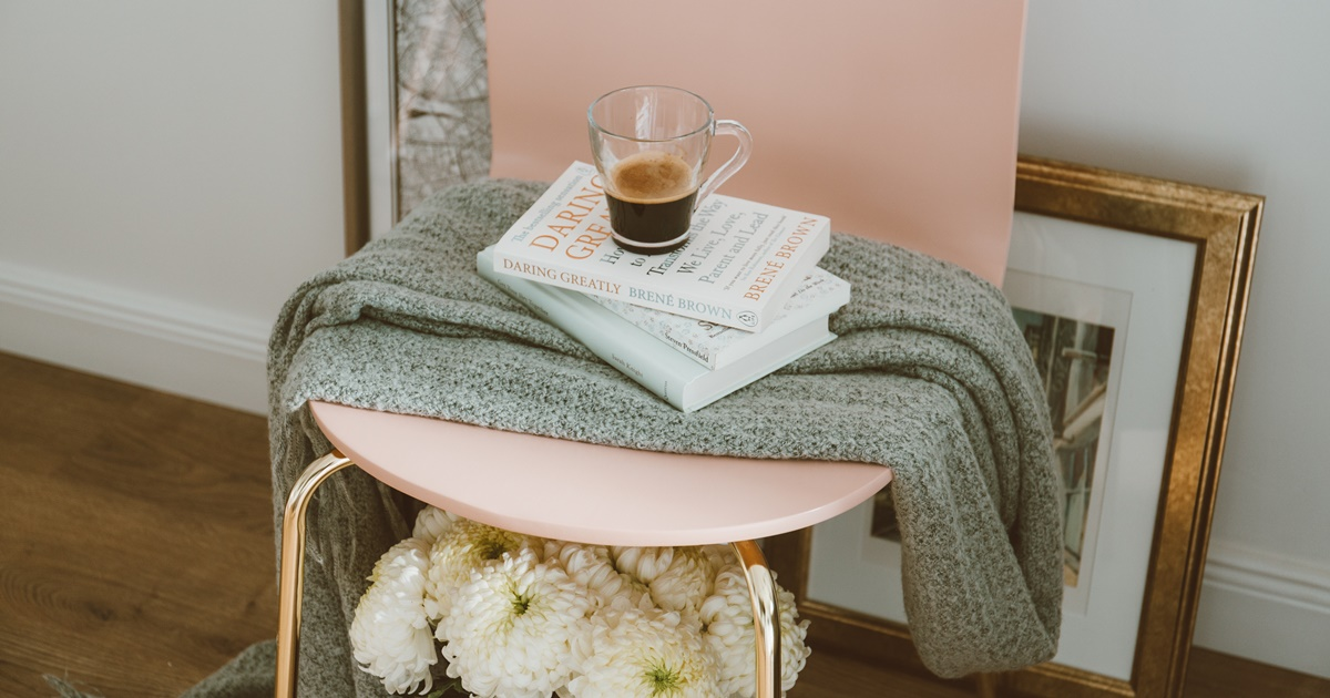 Find Title of Romance Novel, image of pink chair with books sitting atop it, books