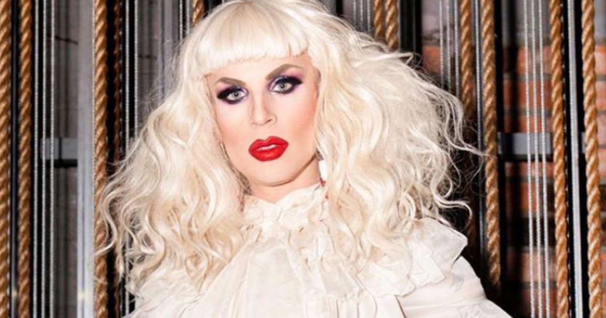 Katya Zamolodchikova posing in front of ropes in a white blouse and black leather skirt
