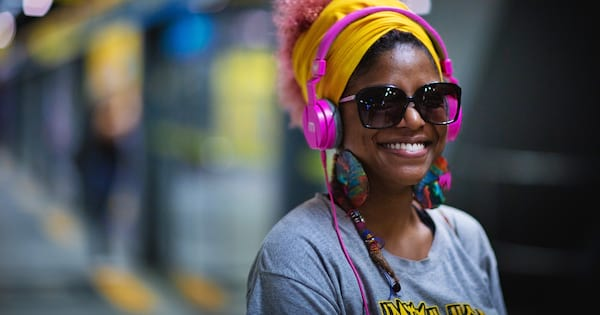 podcasts about books, image of a smiling Black woman wearing hot pink headphones, books