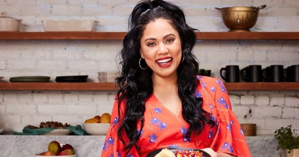 Ayesha Curry holding up a plate of food while posing for the camera