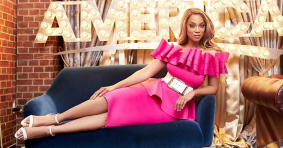 Tyra Banks wearing a bright pink dress with a chunky white belt posing on a blue velvet couch in front of a light up sign that reads 'Good Morning America'