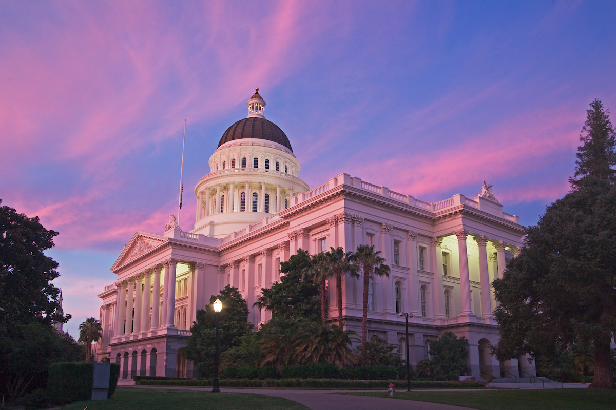 California capitol building at dusk with a purple and pink sunset