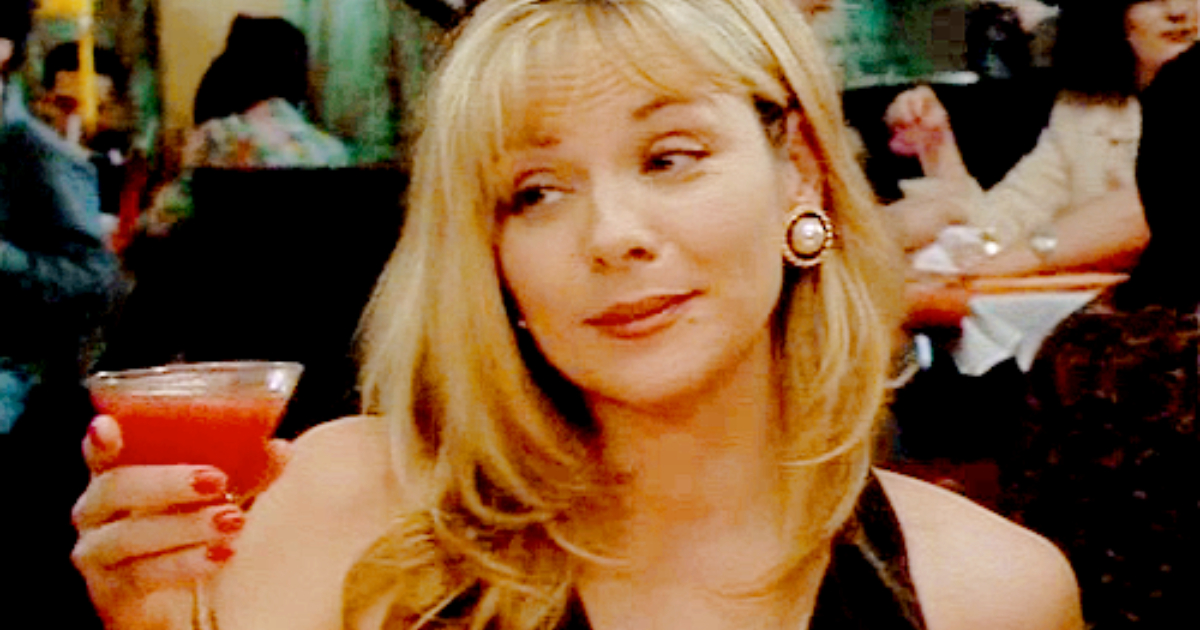 Samantha Jones in a slinky black dress holding up a pink cocktail in her had to cheers in a scene from HBO's 'Sex and the City'