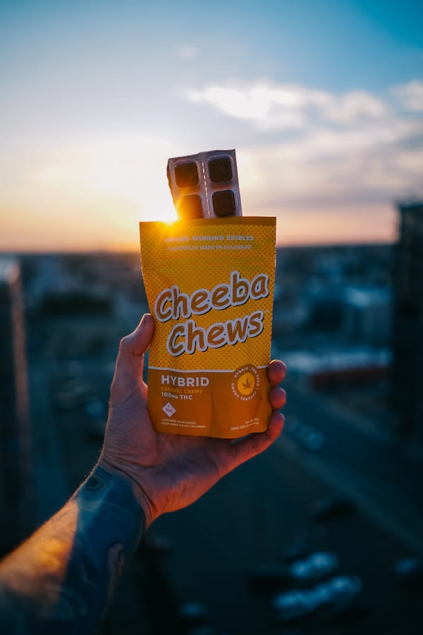 Open packet of Cheeba Chews being held up against the setting sun
