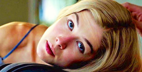 Rosamund Pike as Amy Dunne in the movie adaptation of Gone Girl laying on Ben Affleck looking up at him