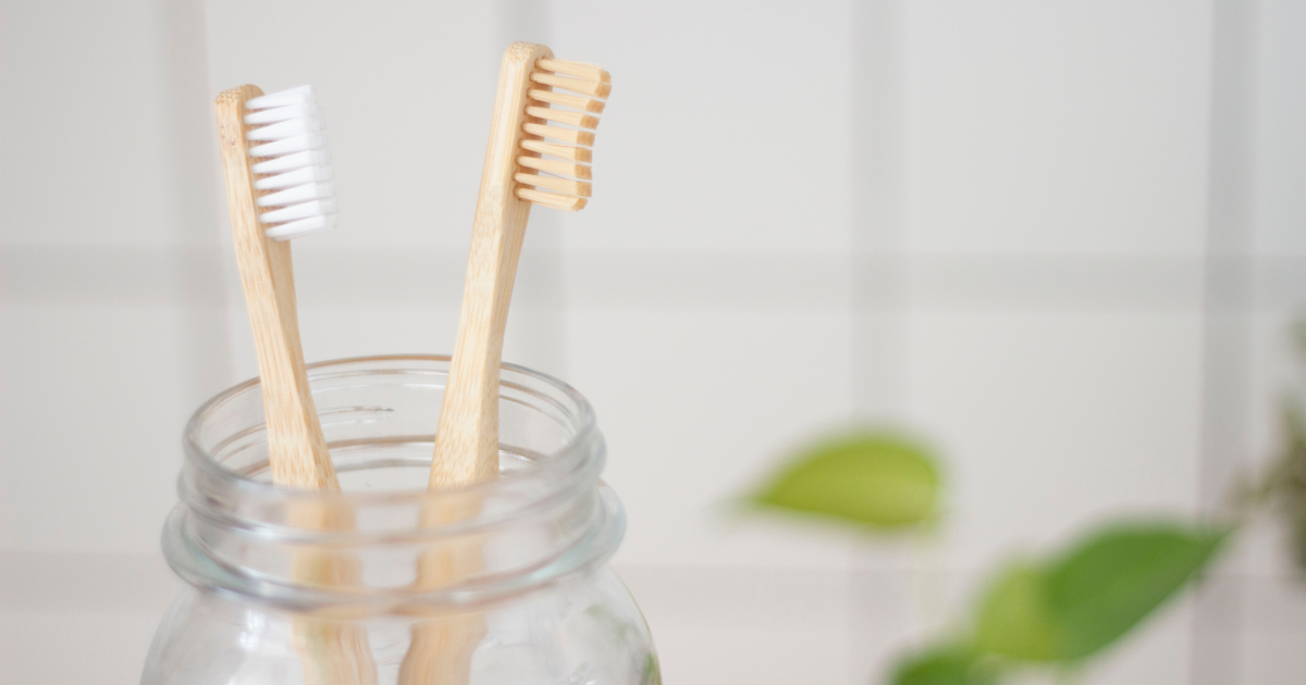 Two bamboo toothbrushes sitting in a mason jar