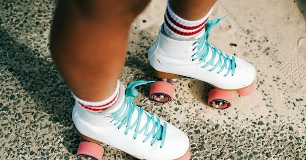 roller derby romance novels, close up of a black person wearing white roller skates with pink wheels, books