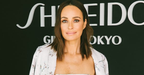 Catt Sadler posing in front of a black backdrop at the Shisheido Malibu Beach House celebrating the launch of her podcast Naked
