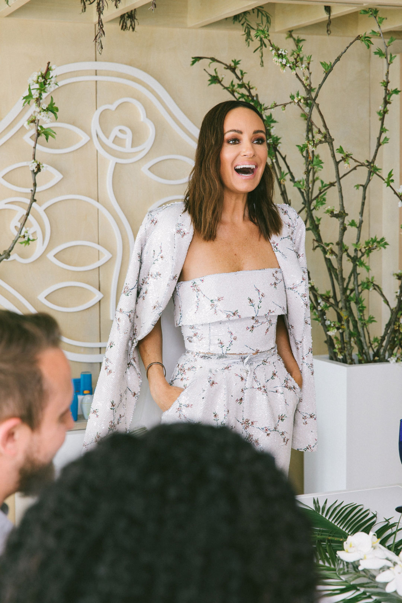Catt Sadler smiling while giving a speech at a lunch celebrating the release of her podcast Naked