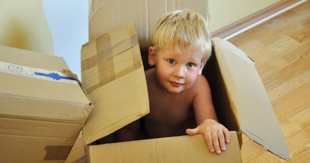 books about moving, photo of a young white child sitting in an empty cardboard box, books
