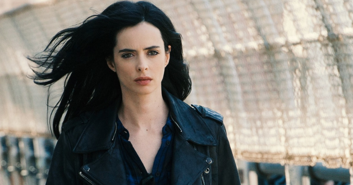 Jessica Jones standing on a bridge with her jet black hair blowing in the wind
