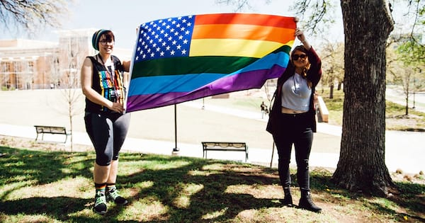 books, two female presenting people holding up a pride flag, lgbt books that have nothing to do with coming out