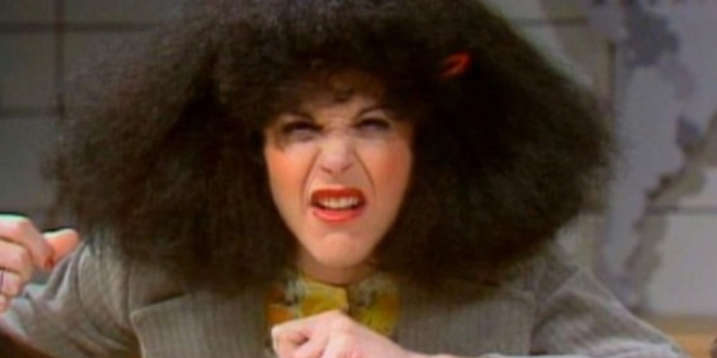 Gilda Radner on SNL wearing a huge black wig making a silly face